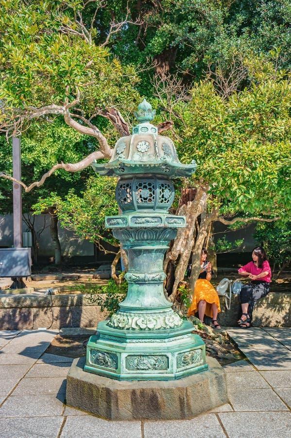 Turistas no identificados que tienen descansar cerca de la linterna japonesa del metal tradicional en el templo de Hasedera, Kama fotos de archivo libres de regalías