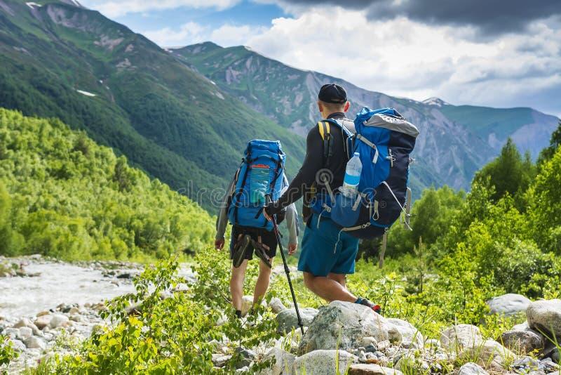 Turistas no passeio na montanha da montanha Dois amigos nas montanhas Caminhada em montes e em montagens Os caminhantes andam na  imagens de stock royalty free