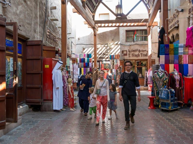 Turistas no souk de matéria têxtil no departamento Dubai foto de stock