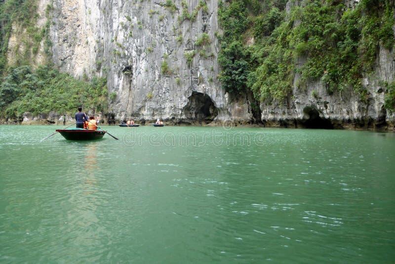 Turistas nos barcos de bambu que visitam em torno das ilhas e das cavernas da baía longa do ha fotos de stock royalty free