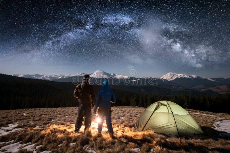 Turistas novos dos pares da vista traseira que têm um resto no acampamento nigh abaixo no céu noturno completamente das estrelas  imagem de stock royalty free