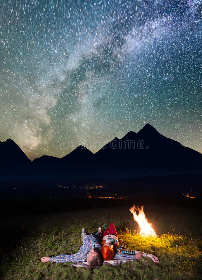 Turistas novos dos pares que encontram-se perto da fogueira sob o céu estrelado incredibly bonito e da Via Látea na noite Luminos fotografia de stock royalty free