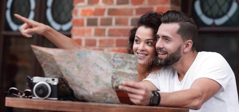 Turistas novos que comem o café no café e que leem o mapa fotografia de stock