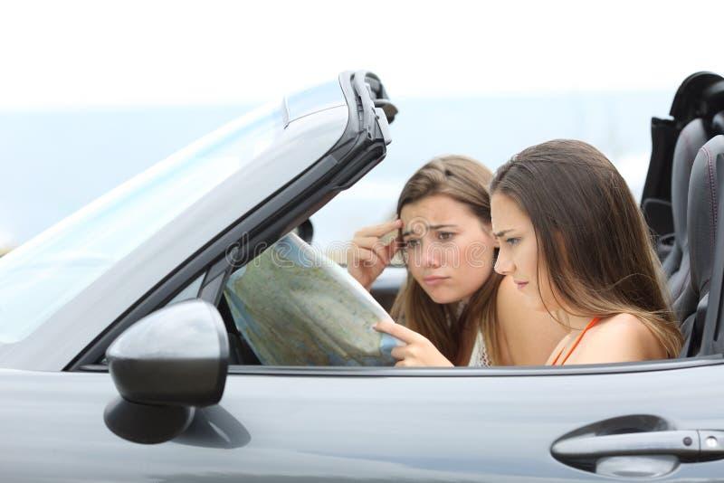 Turistas perdidos que buscan el destino en un coche imagen de archivo
