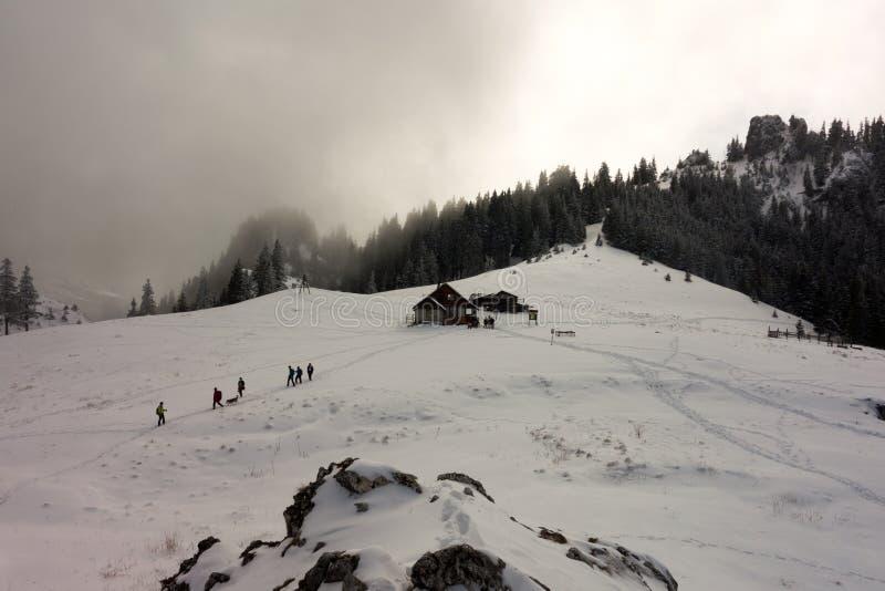 Turistas perto da cabine da montanha imagens de stock royalty free