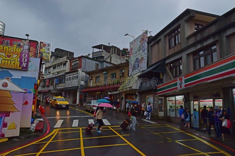 Turistas que acometen para cruzar el camino que tira del equipaje con los paraguas en un día lluvioso en la ciudad moderna de Jiu fotos de archivo