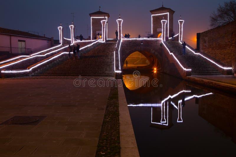 Turistas que andam na ponte Trepponti, Comacchio, Itália na noite imagens de stock