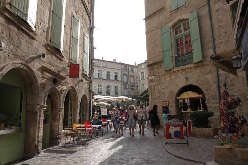 Turistas que andam na rua da cidade turística de Pezenas, Herault em do sul de França imagens de stock royalty free