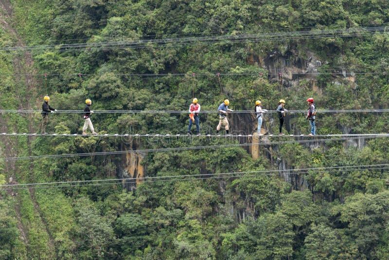 Turistas que andam uma ponte de cabo suspendida em Equador fotografia de stock
