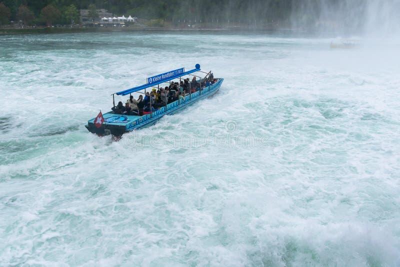 Turistas que apreciam a viagem do barco na cachoeira de Rheinfall em Suíça fotografia de stock royalty free