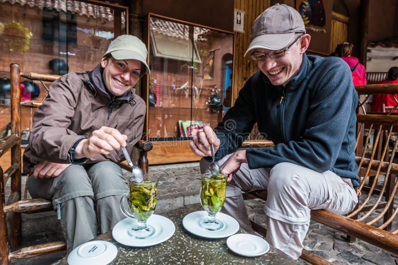 Turistas que beben el té los Andes peruanos Pisac Perú de la coca imagen de archivo