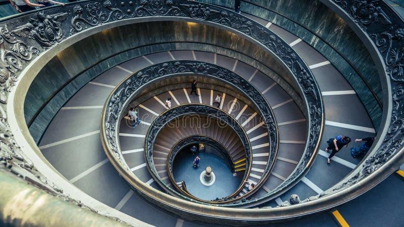 Turistas que caminan abajo de la escalera espiral de Bramante en los museos del Vaticano fotografía de archivo