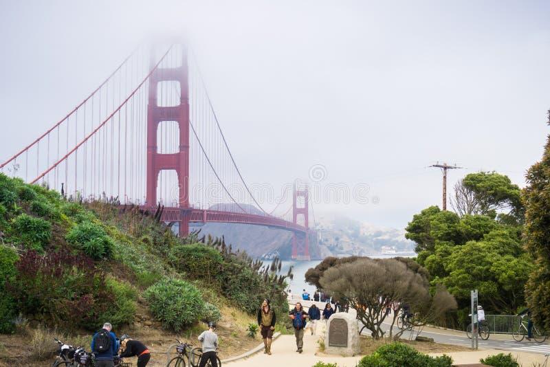 Turistas que caminan al centro que da la bienvenida de puente Golden Gate en un día de niebla foto de archivo libre de regalías