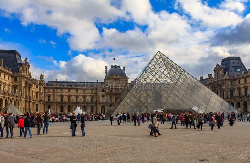 Turistas que caminan delante del famoso la pirámide y el museo del Louvre, uno de los museos de arte más grandes del mundo y un h fotografía de archivo libre de regalías