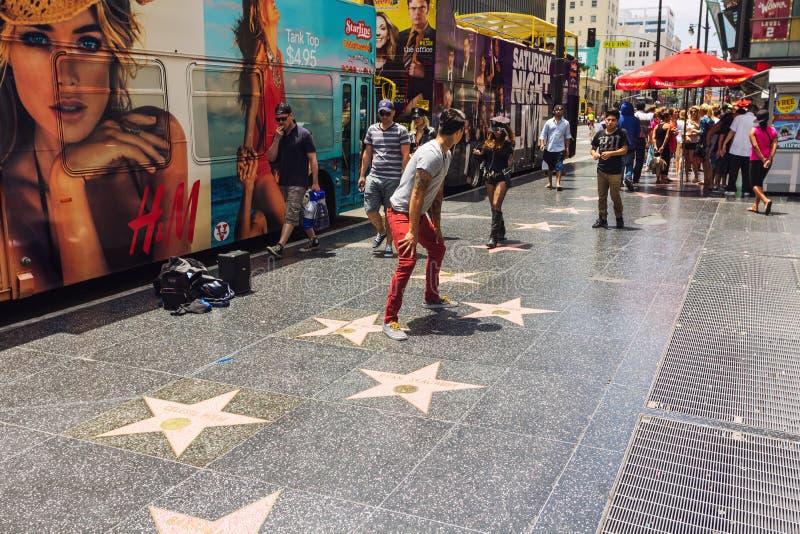 Turistas que caminan en el paseo de Hollywood de la fama foto de archivo