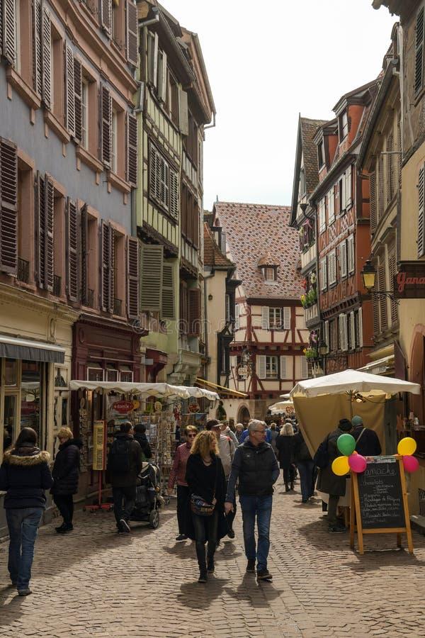 Turistas que caminan a través de las calles en la ciudad mediaval vieja de Colmar fotografía de archivo
