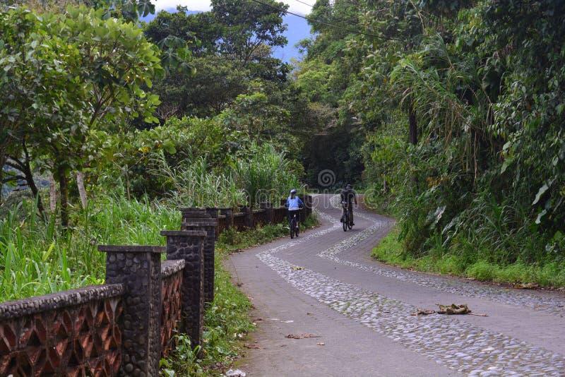 Turistas que caminan y que montan una bici en Baños, Ecuador fotografía de archivo
