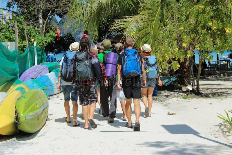 Turistas que caminham com trouxas em uma praia de Phi Island em Tailândia, Ásia foto de stock