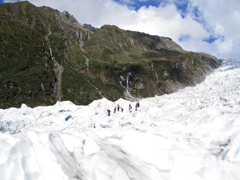 Turistas que caminham na geleira do Fox, Nova Zelândia fotografia de stock royalty free