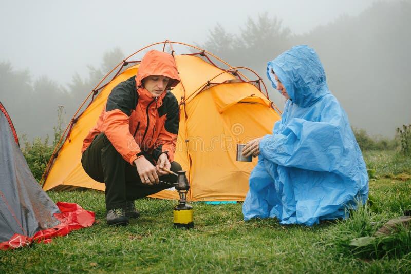 Turistas que cocinan el café cerca de la tienda en las montañas foto de archivo libre de regalías