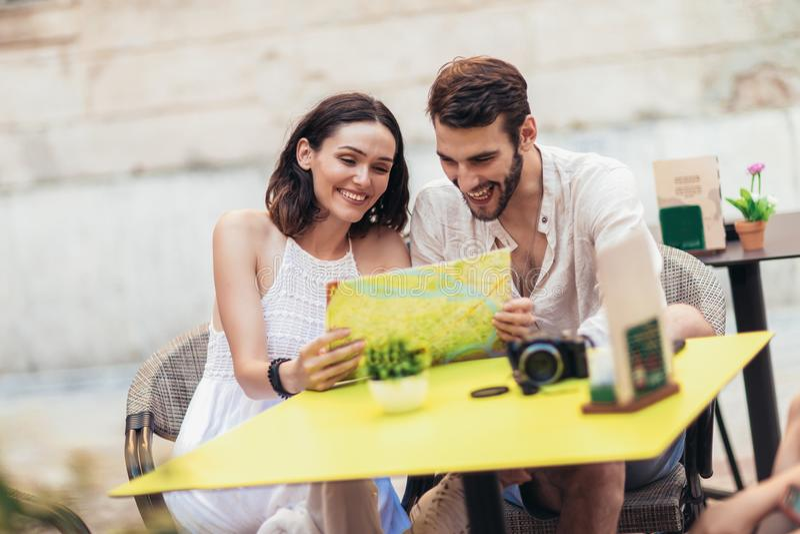 Turistas que comem o café no café e que leem o mapa fotos de stock royalty free