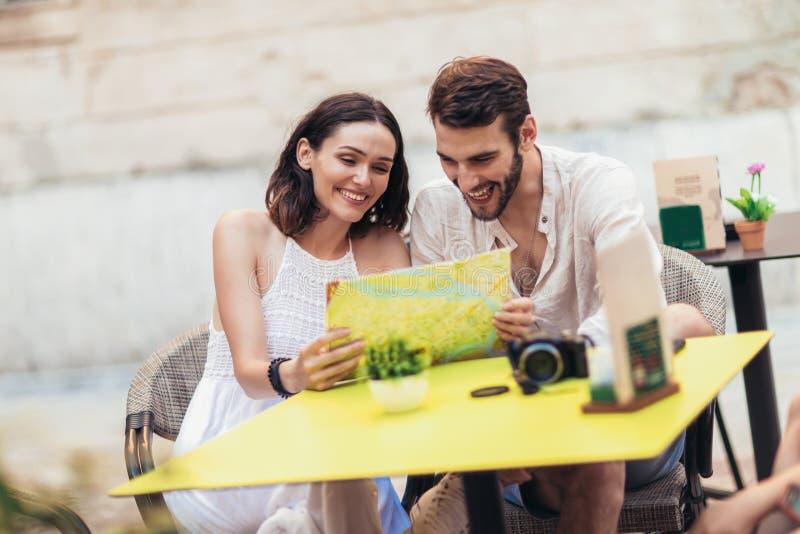 Turistas que comen café en el café y que leen el mapa fotos de archivo libres de regalías
