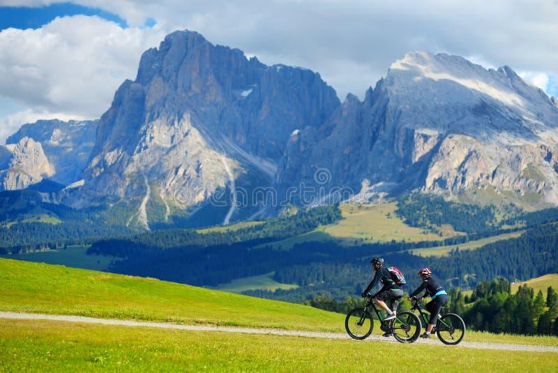 Turistas que dão um ciclo em Seiser Alm, o prado alpino da alta altitude a maior em Europa, aturdindo montanhas rochosas no fundo fotografia de stock