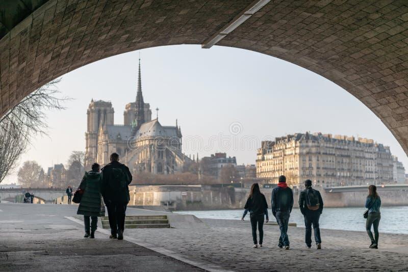 Turistas que dan un paseo en los bancos del Sena debajo del puente Alejandro III con la catedral de Notre Dame en el fondo fotografía de archivo
