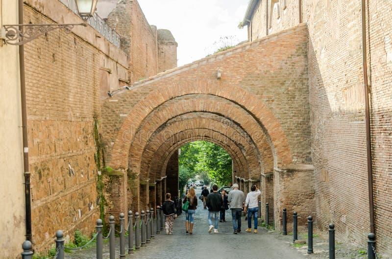 Turistas que dan un paseo a través de las calles históricas antiguas de Roma debajo de los arcos de piedra en el área en la igles fotografía de archivo