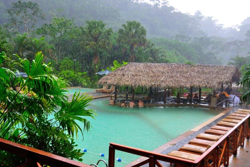 Turistas que disfrutan de los resortes calientes durante la tempestad de la lluvia imagen de archivo libre de regalías