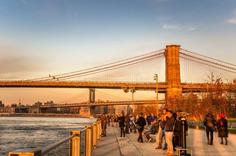 Turistas que disfrutan de una puesta del sol hermosa en el parque del puente de Brooklyn fotos de archivo libres de regalías