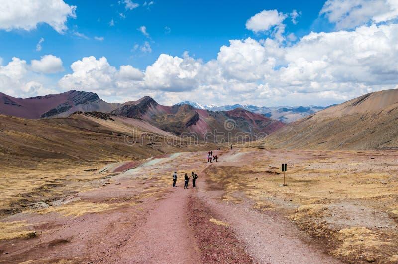 Turistas que emigran en el camino rocoso rojo en montañas del arco iris, Perú imagen de archivo