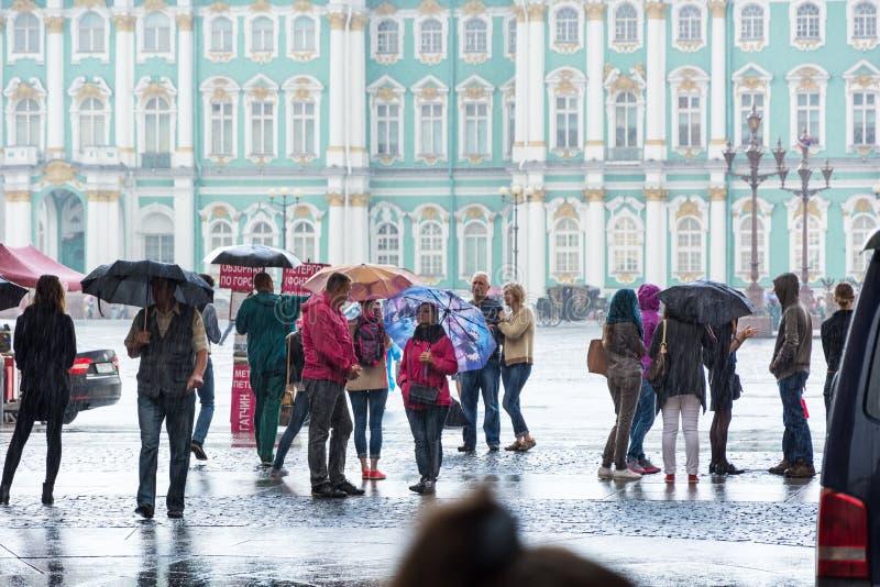 Turistas que escondem da chuva sob o arco do general Staf fotografia de stock royalty free
