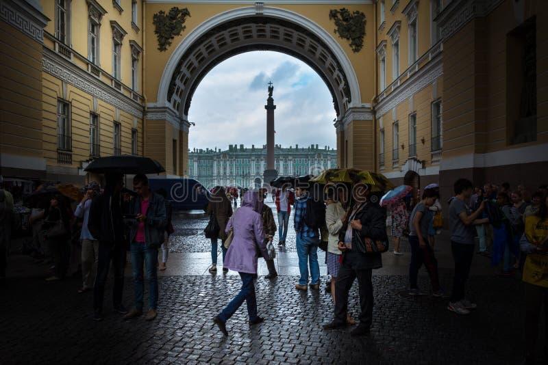 Turistas que escondem da chuva sob o arco do general Staf imagem de stock royalty free