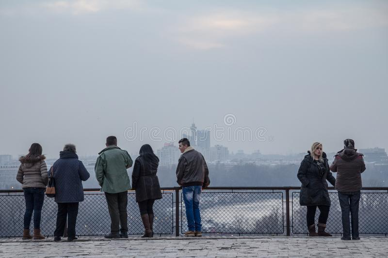 Turistas que estão na fortaleza de Kalemegdan que olha um panorama nevoento de Novi Beograd, a parte a mais moderna de Belgrado fotografia de stock