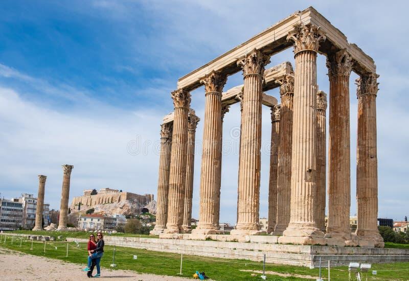 Turistas que estão sendo fotografados na frente do templo grego do olímpico Zeus com a acrópole de Atenas no fundo fotos de stock royalty free