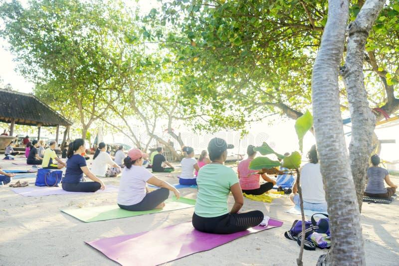 Turistas que exercitam a ioga na praia de Sanur fotografia de stock royalty free