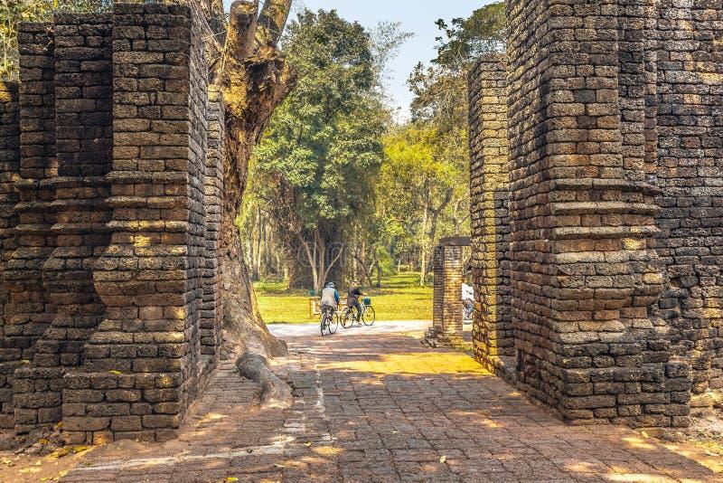 Turistas que exploram o parque histórico de Satchanalai do si antigo com as bicicletas em Tailândia foto de stock