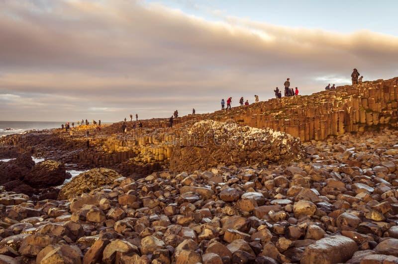Turistas que exploran a través de las columnas formadas hexagonales grandes de las rocas del basalto foto de archivo libre de regalías