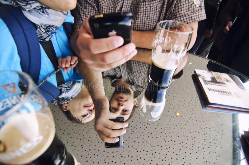 Turistas que gozan de la cerveza de Guinness imagen de archivo