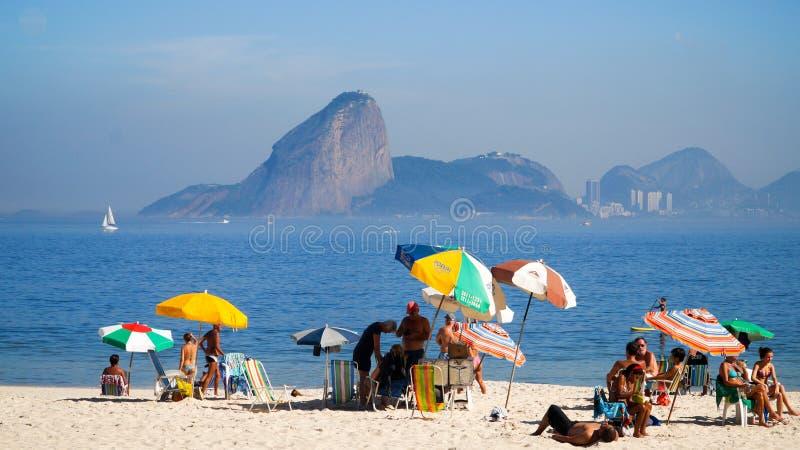 Turistas que gozan de la playa en Niteroi con la opinión sobre Rio de Janeiro, el Brasil imagen de archivo libre de regalías