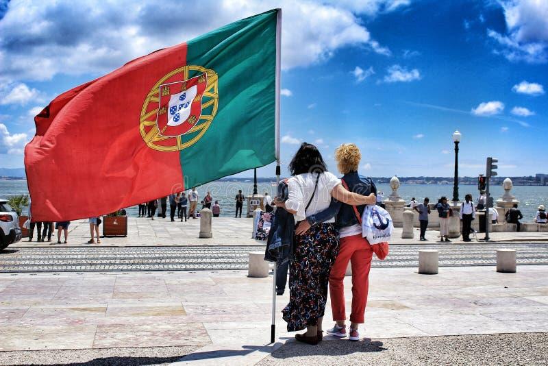 Turistas que guardam a bandeira portuguesa imagem de stock royalty free