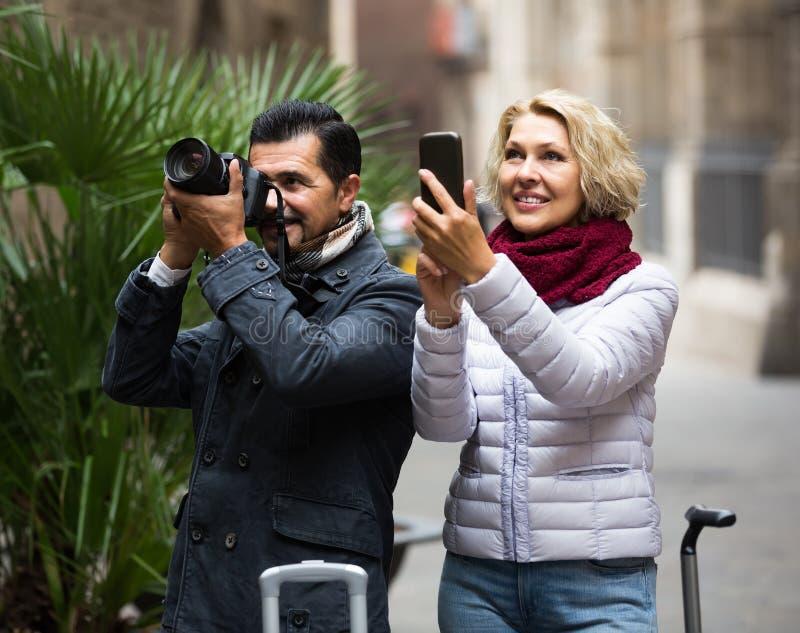 Turistas que hacen turismo y que hacen la foto en cámara y smartphone imagen de archivo libre de regalías