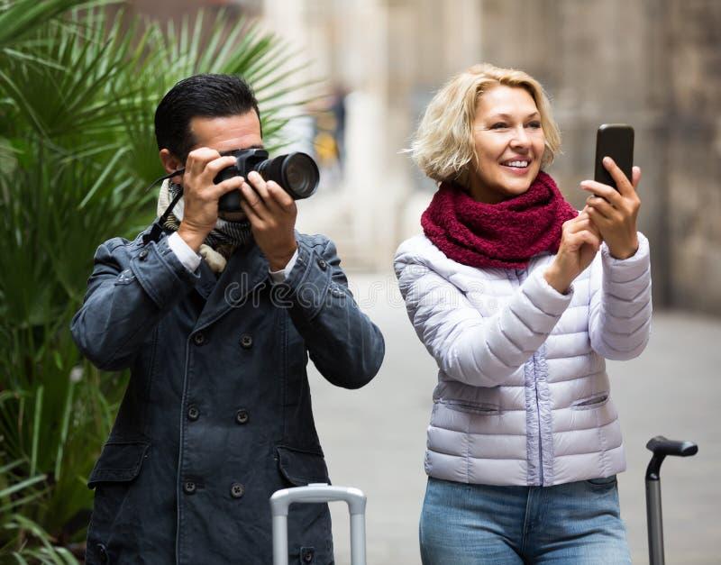 Turistas que hacen turismo y que hacen la foto en cámara y smartphone imagenes de archivo