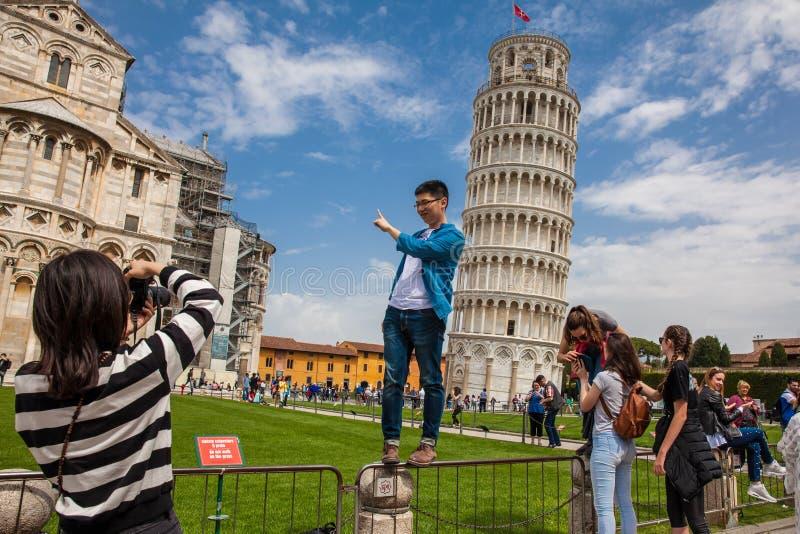 Turistas que levantam e que tomam imagens na frente da torre inclinada famosa de Pisa imagens de stock