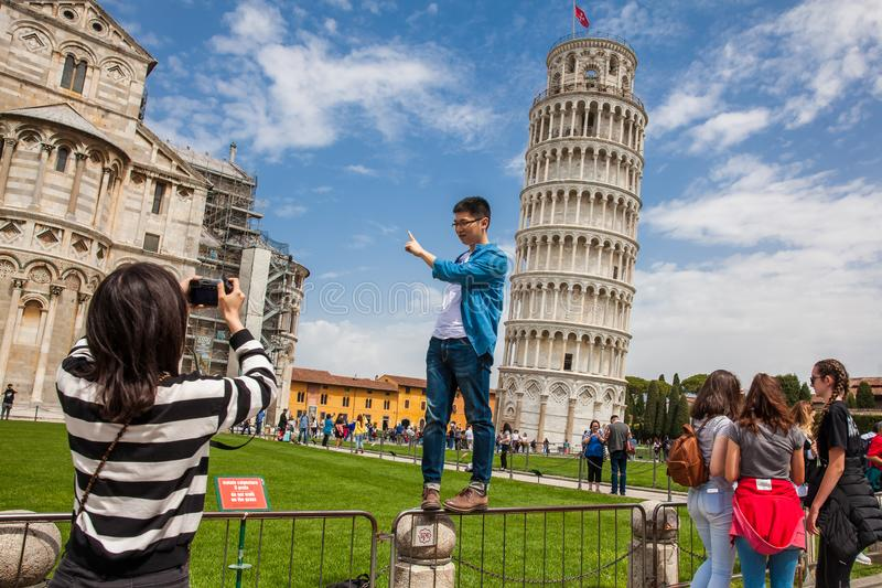 Turistas que levantam e que tomam imagens na frente da torre inclinada famosa de Pisa imagem de stock royalty free