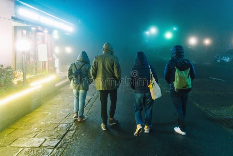 Turistas que llevan la capa y que caminan en la calle con las luces en la noche mientras que llueve en invierno en Alishan, Taiw? foto de archivo libre de regalías