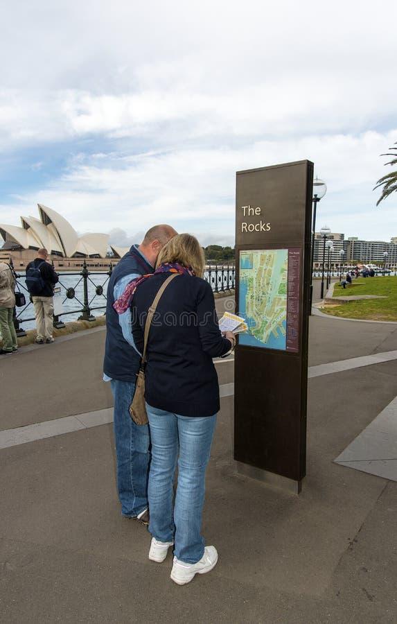 Turistas que miran la correspondencia de las rocas imagenes de archivo