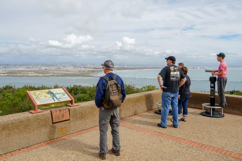 Turistas que miran la vista escénica del centro de la ciudad de San Diego del monumento nacional de Cabrillo imagenes de archivo