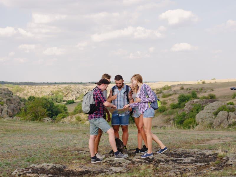 Turistas que miran una correspondencia Mapa de la demostración de la guía en un fondo natural Ir de excursión concepto Copie el e foto de archivo libre de regalías